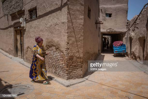Uyghur woman walks through the street of the Kashgar old town northwestern Xinjiang Uyghur Autonomous Region in China Kashgar is located in the north...