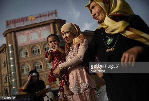 Uyghur woman walks with her baby at a market on August 1 2014 in old Kashgar Xinjiang Uyghur Autonomous Region China Nearly 100 people have been...