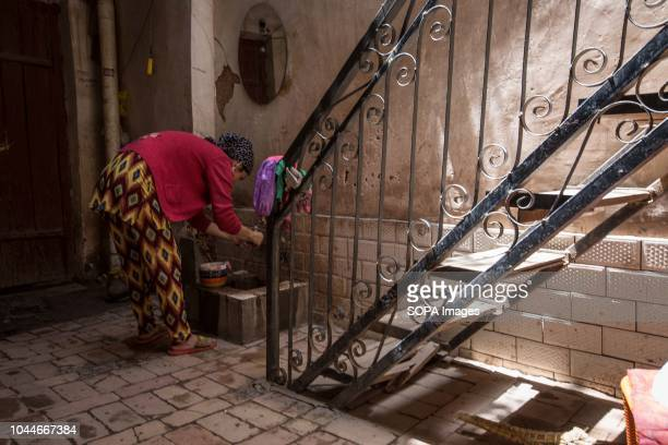 Uyghur woman washes the dishes after the lunch inside the living room of her house in the Kashgar old town, northwestern Xinjiang Uyghur Autonomous...