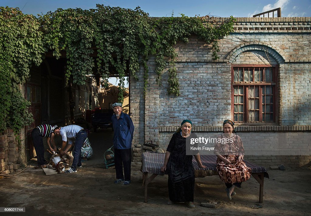 Uyghur women sits in front of their house as her family slaughters a goat, left, on the morning of the Corban Festival on September 12, 2016 in Turpan County, in the far western Xinjiang province, China. The Corban festival, known to Muslims worldwide as Eid al-Adha or 'feast of the sacrifice', is celebrated by ethnic Uyghurs across Xinjiang, the far-western region of China bordering Central Asia that is home to roughly half of the country's 23 million Muslims. The festival, considered the most important of the year, involves religious rites and visits to the graves of relatives, as well as sharing meals with family. Although Islam is a 'recognized' religion in the constitution of officially atheist China, ethnic Uyghurs are subjected to restrictions on religious and cultural practices that are imposed by China's Communist Party. Ethnic tensions have fueled violence that Chinese authorities point to as justification for the restrictions.