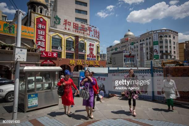 Uyghur women walk in the Tianshan District knows as the Uyghur district of Urumqi capital of northwest China's Xinjiang Uyghur Autonomous Region in...