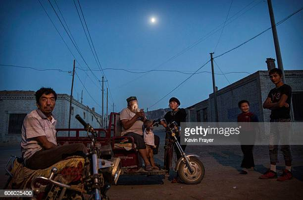 Uyghurs gather in the street of a village outside before the Corban Festival on September 11 2016 in Turpan County in the far western Xinjiang...