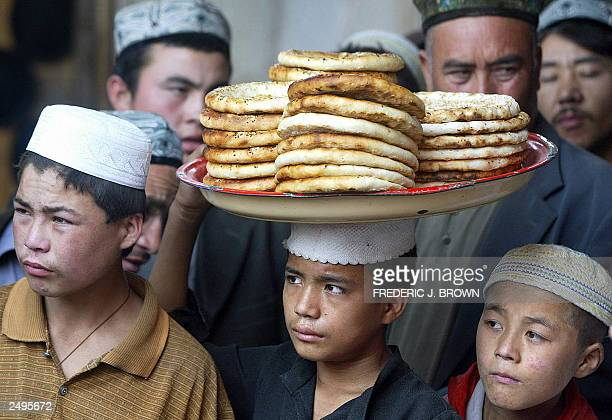 A Uygur boy carries a tray of flat bread balanced on his head for sale in a bazaar in Hotan a desert town along the southern boundary of the...