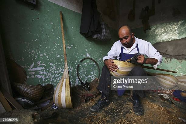 Uygur craftsman makes a traditional musical instrument at his workshop on September 22, 2006 in Kashi of Xinjiang Uygur Autonomous Region, northwest...