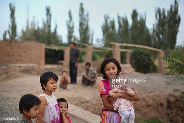 Uygur girl holds her young brother near her house on August 18 2010 in Turpan of Xinjiang Autonomous Region China Turpan basin is the second lowest...