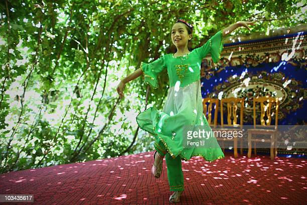 Uygur girl performs dance for visitors in her house on August 18 2010 in Turpan of Xinjiang Autonomous Region China Turpan basin is the second lowest...
