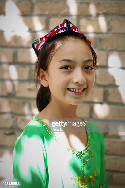 Uygur girl poses for photo in her house on August 18 2010 in Turpan of Xinjiang Autonomous Region China Turpan basin is the second lowest continental...