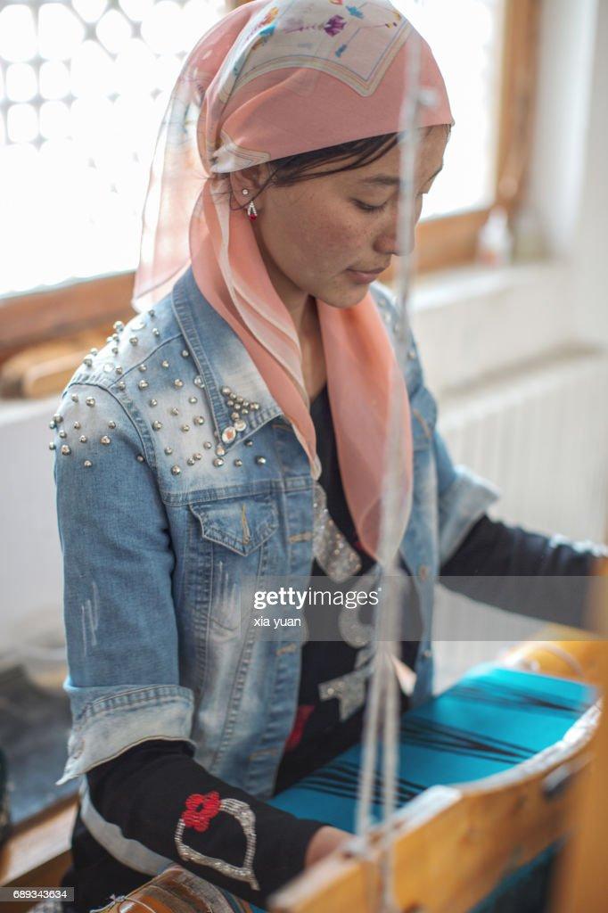 A Uygur girl weaving the Atlas Silk at loom,Hotan,China : Stock Photo