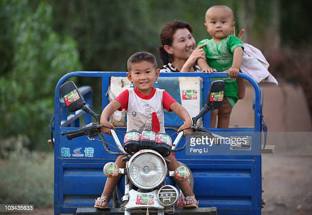 Uygur little girl sits on the driver's seat of threewheeled automobile on August 18 2010 in Turpan of Xinjiang Autonomous Region China Turpan basin...