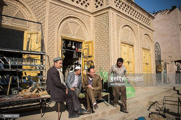 Uygur men were sitting out of a blacksmith shop and talking about out something.