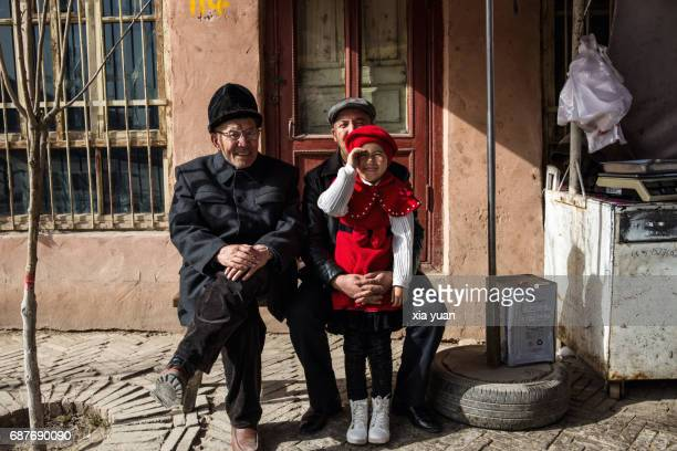 uyhgur girl,grandfather and father sharing the happiness of a family union,kashgar,china - uygur culture photos et images de collection