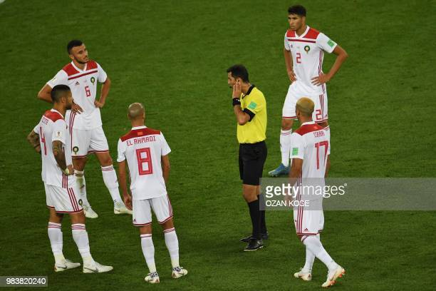 Uzbek referee Ravshan Irmatov waits for the VAR goal review confirming Spain's second goal during the Russia 2018 World Cup Group B football match...