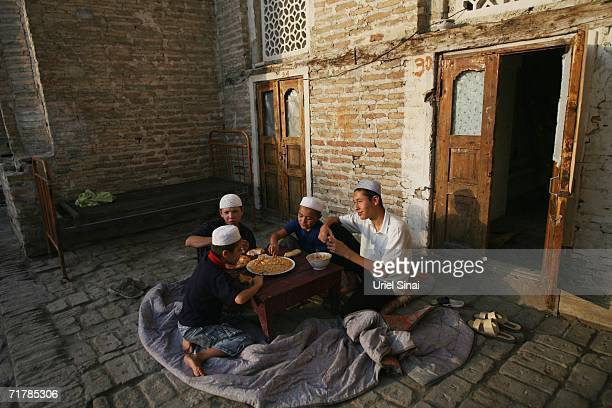 Uzbek youths eat their dinner in the courtyard of the local mosque and madrasa where they live and study Islam on August 12 2006 in Kukand near...