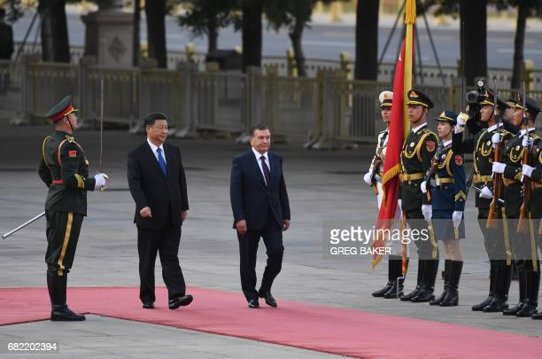 Uzbekistan President Shavkat Mirziyoyev reviews an honour guard with Chinese President Xi Jinping during a welcome ceremony outside the Great Hall of...
