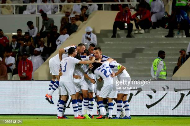 Uzbekistan team players celebrate the first goal of the match during the 2019 AFC Asian Cup group F football match between Uzbekistan and Oman at...
