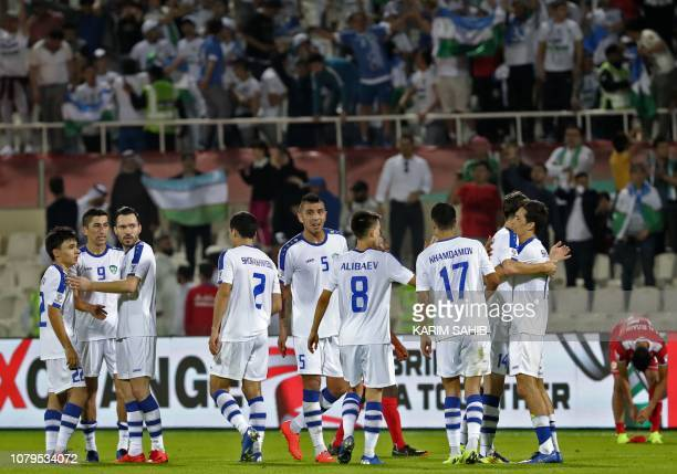 Uzbekistan team players celebrate their 21 win during the 2019 AFC Asian Cup group F football match between Uzbekistan and Oman at Sharjah stadium in...