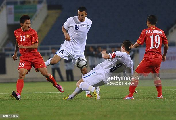Uzbekistan's Fozil Musaev and Server Djeparov fight for the ball with Vietnam's Pham Thanh Luong and Nguyen Quang Hai during an Asian Cup 2015's...