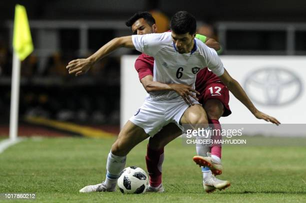 Uzbekistan's Jaloliddin Masharipov fights for the ball with Qatar's Jassem Omer during the men's football preliminary Group B match between Qatar and...