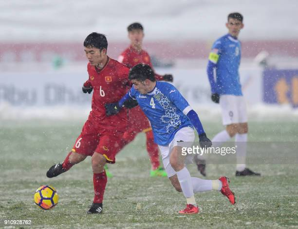 Uzbekistan's Komilov Akramjon competes for the ball with Vietnam's Luong Xuan Truong during their AFC Under23 Championship final football match in...