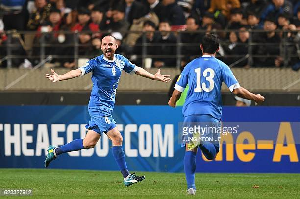 Uzbekistan's Marat Bikmaev celebrates his goal with teammate against South Korea during their 2018 World Cup qualifying football match in Seoul on...