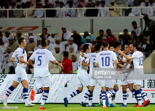 Uzbekistan's midfielder Odil Akhmedov celebrates with teammates the first goal of the match during the 2019 AFC Asian Cup group F football match...