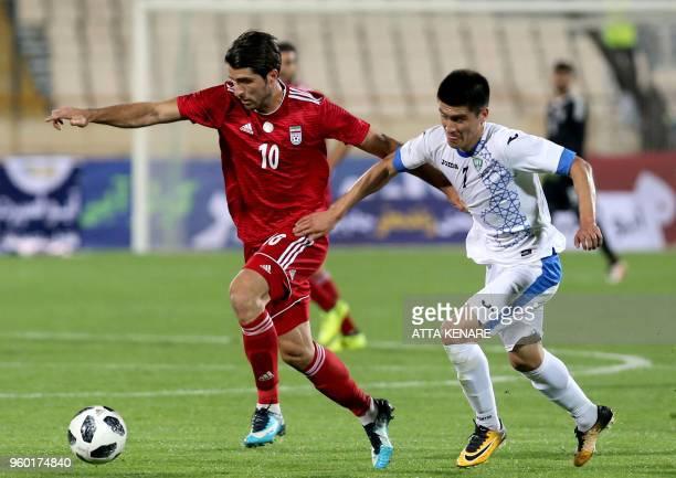 Uzbekistan's midfielder Odiljon Hamrobekov vies for the ball against Iran's forward Karim Ansarifard during their international friendly match at...