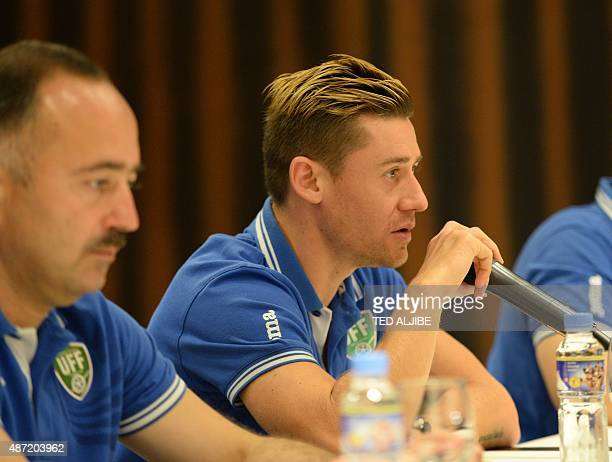 Uzbekistan's player Djeparov Server speaks as head football coach Samvel Babayan listens during a prematch press conference in Manila on September 7...