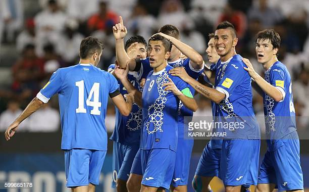 Uzbekistan's players celebrate after scoring a goal during the World Cup 2018 Asia qualification football match between Uzbekistan and Qatar at the...