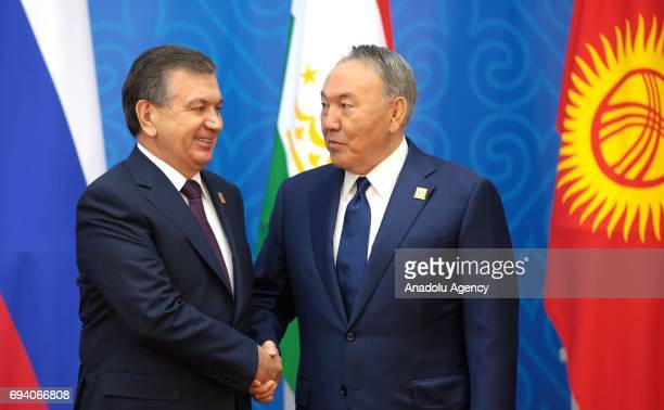 Uzbekistan's President Shavkat Mirziyoyev and Kazakhstan's President Nursultan Nazarbayev shake their hands ahead of a meeting of the Shanghai...