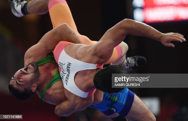 Uzbekistan's Rustam Assakalov competes with India's Harpreet Singh in the men's GrecoRoman 87kg semifinal wrestling competition at the 2018 Asian...