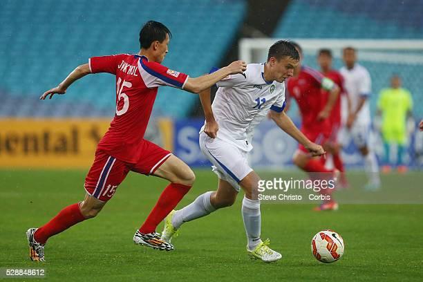 Uzbekistan's Sardor Rashidov is tackled by Jang Kuk Chol from DPR Korea at Stadium Australia Sydney Australia Saturday 10th January 2015