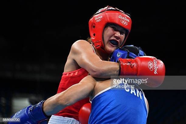 Uzbekistan's Yodgoroy Mirzaeva clinches to Canada's Mandy Marie Brigitte Bujold during the Women's Fly match at the Rio 2016 Olympic Games at the...