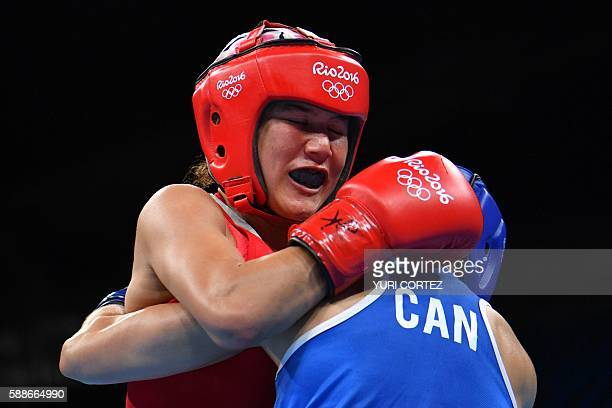 Uzbekistan's Yodgoroy Mirzaeva fights Canada's Mandy Marie Brigitte Bujold during the Women's Fly match at the Rio 2016 Olympic Games at the...