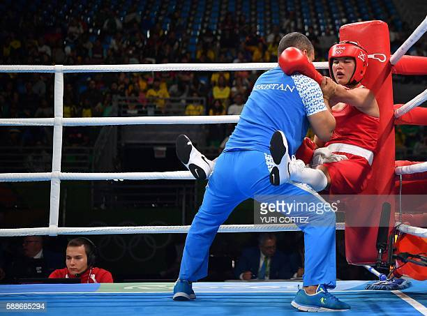 Uzbekistan's Yodgoroy Mirzaeva is attended to as she fights Canada's Mandy Marie Brigitte Bujold during the Women's Fly match at the Rio 2016 Olympic...