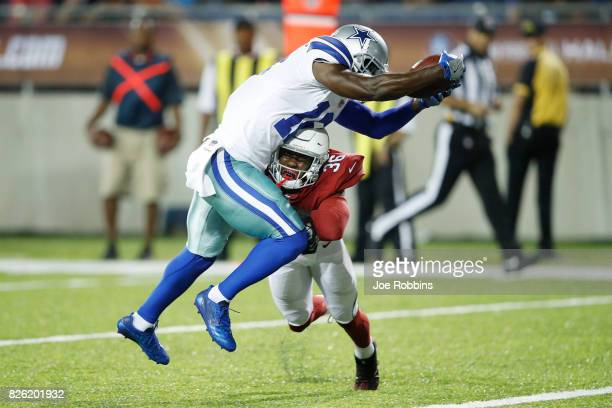 Uzoma Nwachukwu of the Dallas Cowboys leaps into the end zone for a 14yard touchdown ahead of Budda Baker of the Arizona Cardinals in the third...