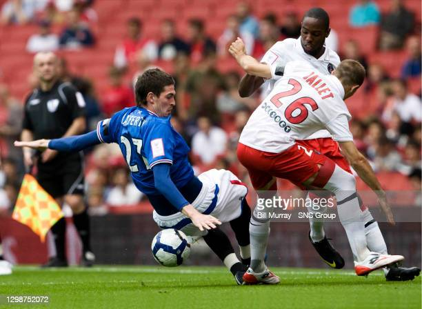V RANGERS.EMIRATES STADIUM - LONDON.Kyle Lafferty loses his footing under pressure from PSG's Christophe Jallet and Jean-Eudes Maurice