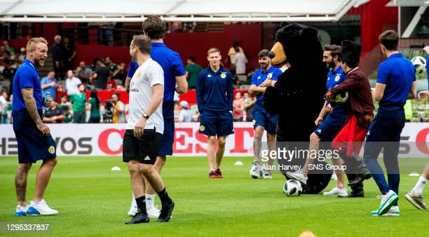 V SCOTLAND.MEXICO .Scotland's Graeme Shinnie is tackled by a furry mascot as the players look around the pitch