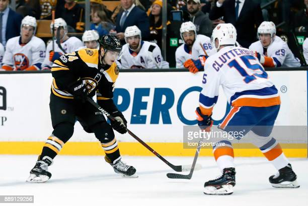 v74 gains the blue line watched by New York Islanders right wing Cal Clutterbuck during a game between the Boston Bruins and the New York Islanders...