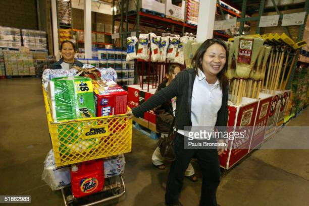 Va Vang walks with the shopping cart as her sister Bao Lee leads the way while they buy groceries at Costco's supermarket December 11 2004 in Fresno...