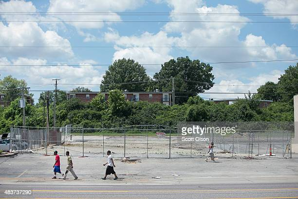 A vacant lot that was once home to a beauty supply store as people walk past along West Florrisant Avenue one year after the shooting of Michael...