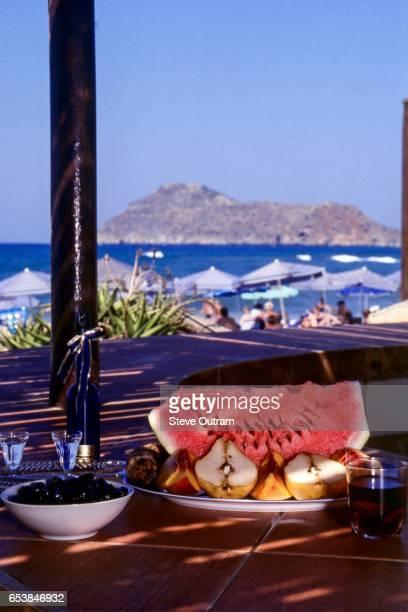 Vacation Food. Fresh Fruit Salad, Black Olives, Glasses of Red Wine and Tsikouda (Raki) at a Taverna by the sea, Platanias, Crete, Greece