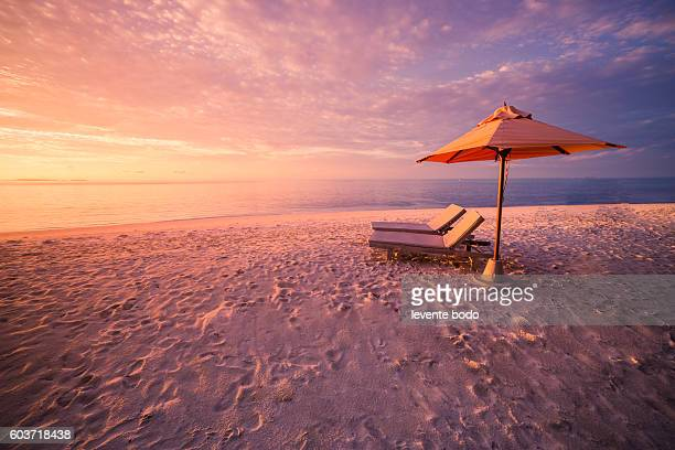 vacation holidays background wallpaper - two beach lounge chairs under tent on beach - tropical island sunset stock pictures, royalty-free photos & images