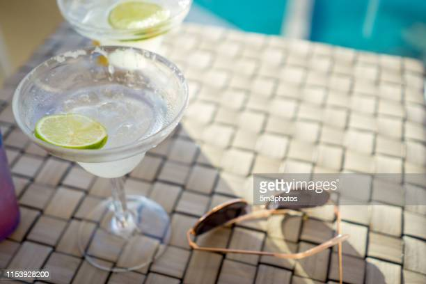 vacation lifestyle sunglasses and alcohol lime drink items at resort pool - margarita beach stock photos and pictures