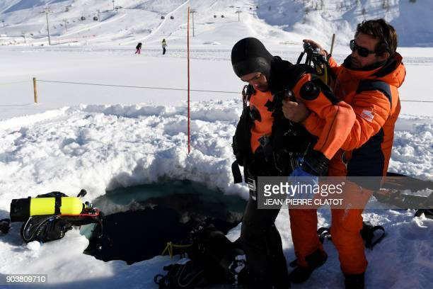 A vacationer wearing special equipment is being helped as he exits a hole after ice diving at minus two degrees Celsius in the frozen lake of Val...