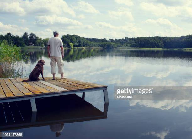 Vacationer with dog overlooking lake from landing stage with blue skies in background