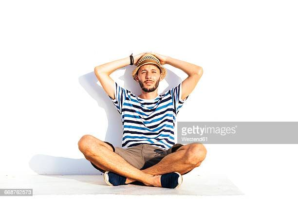Vacationer with straw hat and striped t-shirt sitting on spur leaning against white wall