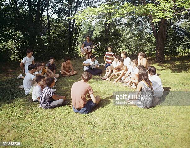 Vacationers at the Pine Grove Motel seated in a circle having a sing along
