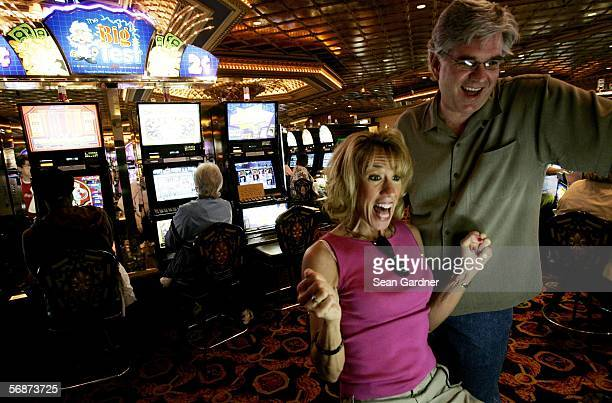 Vacationers Laura Mazzarella and Mark Reedy of Baltimore, Maryland celebrate winning after a couple of spins on the slot machines at Harrah's Casino...