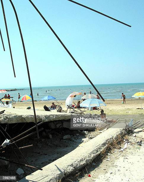 Vacationers lie on the Durres beach close to the ruins of a demolished building 05 August 2003 The Albanian government in an effort to make better...