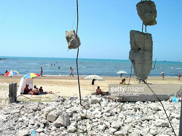 Vacationers lie on the Durres beach close to the ruins of a demolished building 05 August 2003 The Albanian government in an effort to make a better...